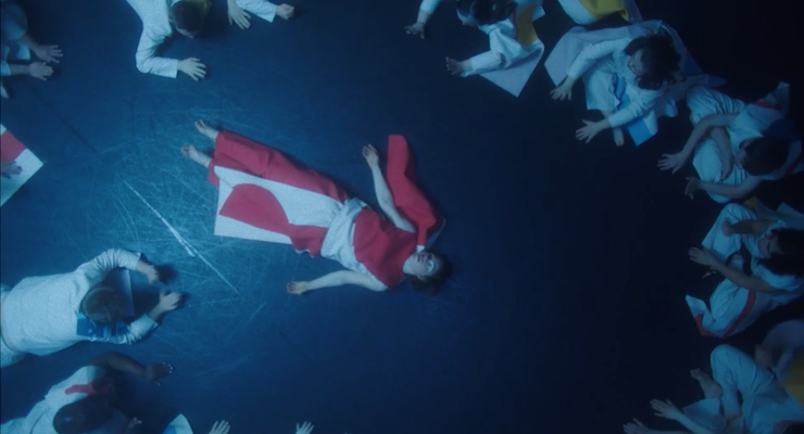 The Chosen One lying on the floor surrounded by the other dancers