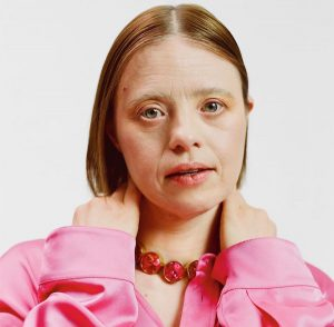 Sarah Gordy head shot, wearing pink silk blouse