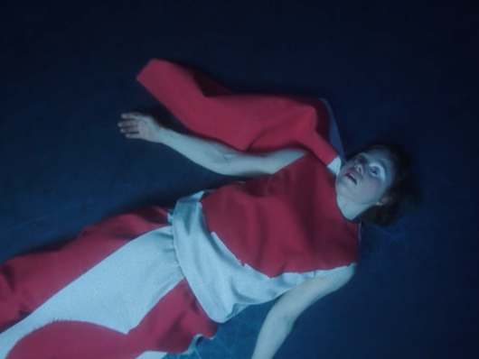 The Chosen One, played by Sarah, exhausted on floor after dancing to her death